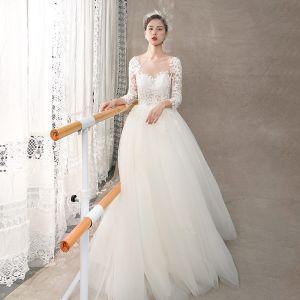 Illusion Ivory / Creme Durchsichtige Brautkleider / Hochzeitskleider 2018 A Linie Rundhalsausschnitt Lange Ärmel Rückenfreies Applikationen Spitze Sweep / Pinsel Zug Rüschen