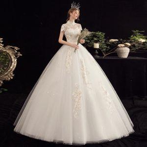 Prisvärd Champagne Bröllopsklänningar 2020 Balklänning Genomskinliga Hög Hals Korta ärm Appliqués Spets Beading Pärla Paljetter Långa Ruffle
