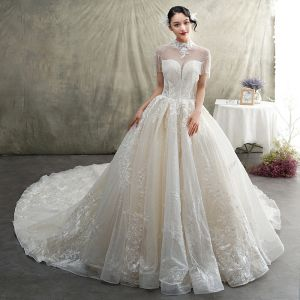 Luxury / Gorgeous Champagne See-through Wedding Dresses 2019 Princess High Neck Short Sleeve Backless Appliques Lace Beading Tassel Glitter Tulle Cathedral Train Ruffle