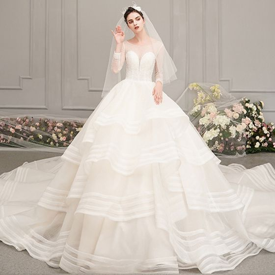 d3171e52f39d luxury-gorgeous-ivory-see-through-wedding-dresses-2019-ball-gown-scoop-neck- 3-4-sleeve-backless-beading-cathedral-train-cascading-ruffles-560x560.jpg